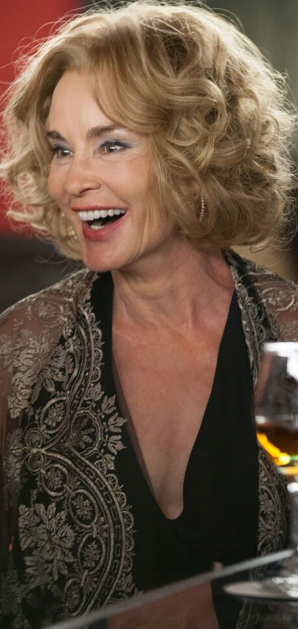 Jessica Lange laughing at a bar while wearing a dress and shawl