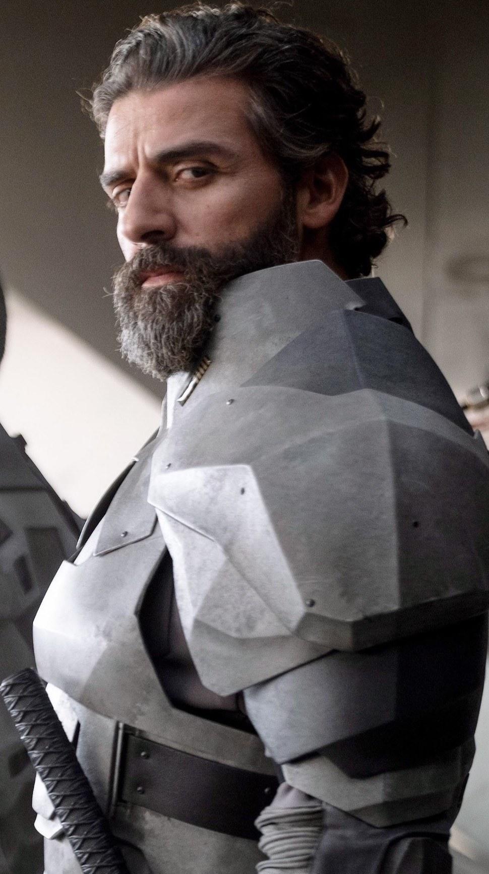 Oscar Isaac with long hair, a long beard, and wearing silver armor