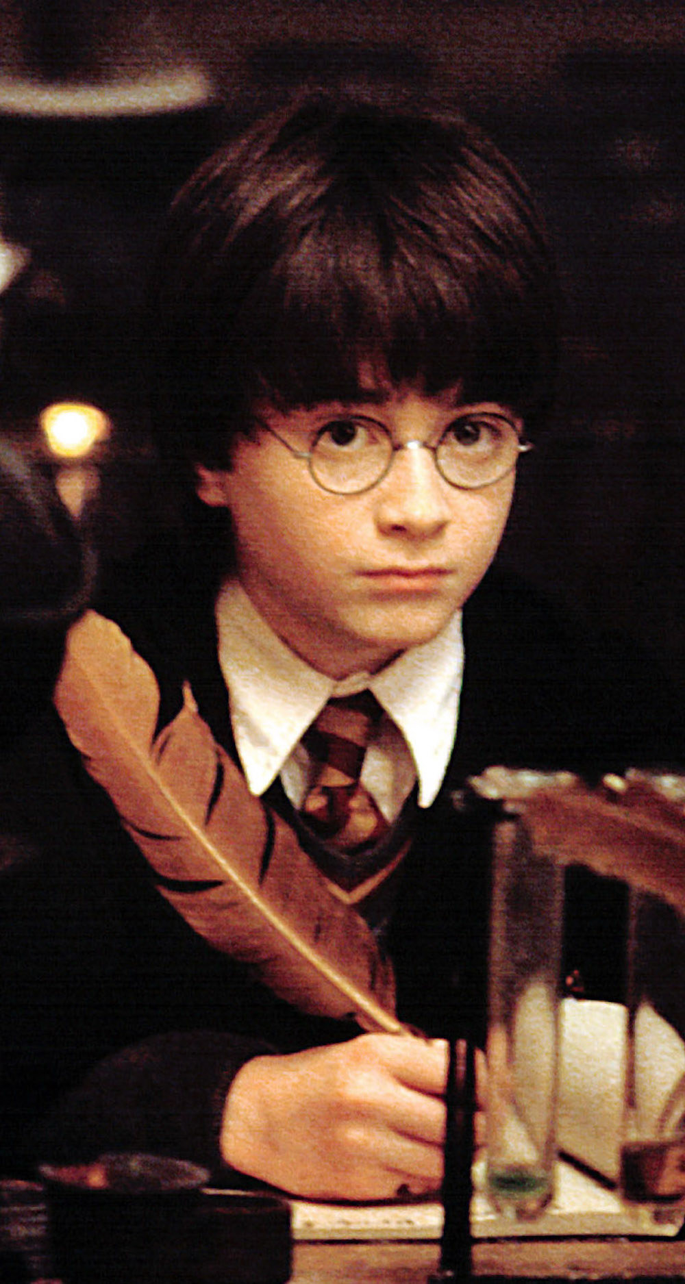 Daniel Radcliffe wearing round glasses while in a Hogwarts school uniform, writing