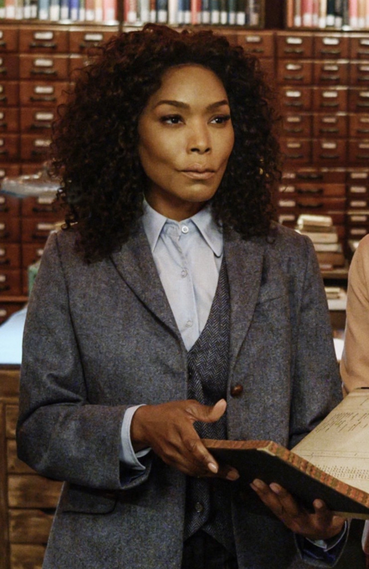 Angela Bassett wearing a three-piece suit while holding a book