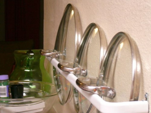 Use a small curtain rod to store lids for easy access.