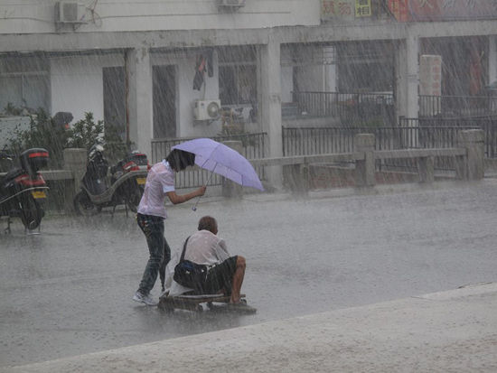 A girl walks beside a disabled beggar crawling home on a makeshift wooden cart in the rain.