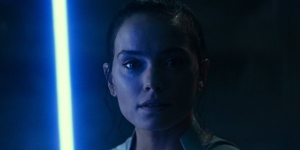 Rey under the blue glow of her lightsaber