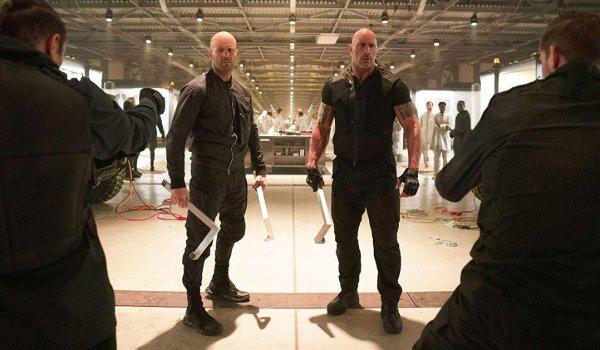Hobbs & Shaw debout avec des pipes, alors que des armes à feu sont tracées sur la base secrète