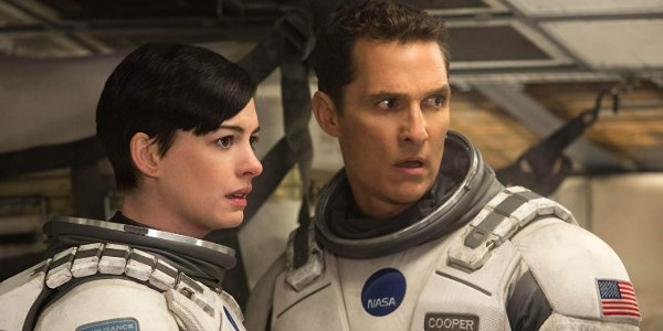 Interstellar Brand and Cooper look across the room with concern