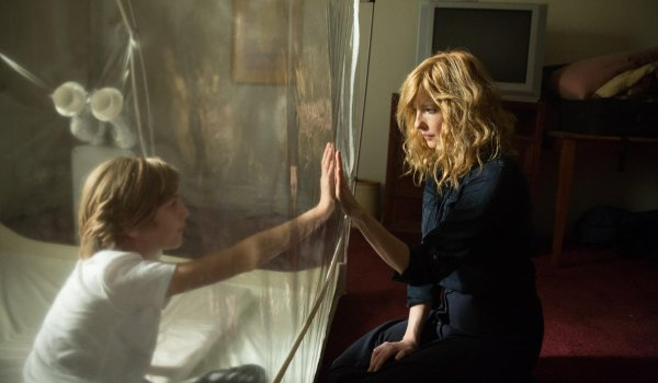 Eli Kelly Reilly looks at her son through a plastic bubble