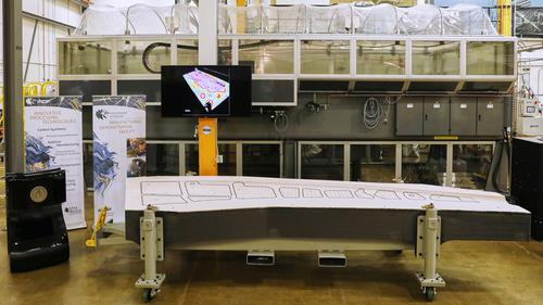 A 3D-printed trim and drill tool developed by ORNL and Boeing to be used in building Boeing's 777X passenger jet has received the title of largest solid 3D-printed item by Guinness World Records. In the background is the Big Area Additive Manufacturing (BAAM) machine researchers used to build the tool. (Source: Oak Ridge National Laboratory)