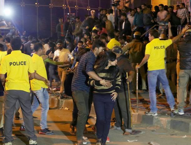 Nesta imagem de 1º de janeiro, um homem (C) ajuda uma mulher indiana a se desvencilhar da multidão nas celebrações de ano-novo enquanto policiais tentam conter grupos exaltados