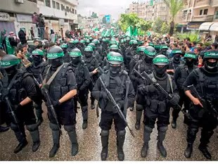 In this December 14, 2014, file photo, masked Palestinian gunmen of the Hamas militant grouphold weapons during a rally to commemorate the 27th anniversary of the group in Gaza City. Amnesty International on Wednesday, May 27, 2015, accused the militant group of abducting, torturing and killing Palestinians during the war in the Gaza Strip summer 2014, saying some of the actions amount to war crimes.