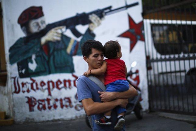 A man walks past a mural depicting late Venezuelan President Hugo Chavez near hi