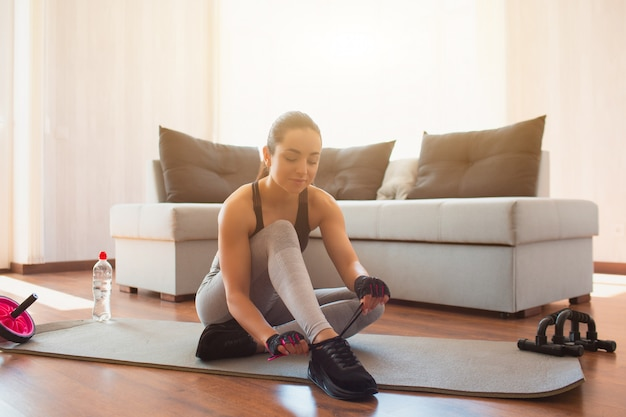 jovem-mulher-a-fazer-exercicios-de-esporte-no-quarto-durante-a-quarentena-sente-se-no-tapete-e-nos-cadarcos-dos-sapatos-preparando-se-para-o-treino-em-casa_186523-1284 Perder barriga rápido é possível?