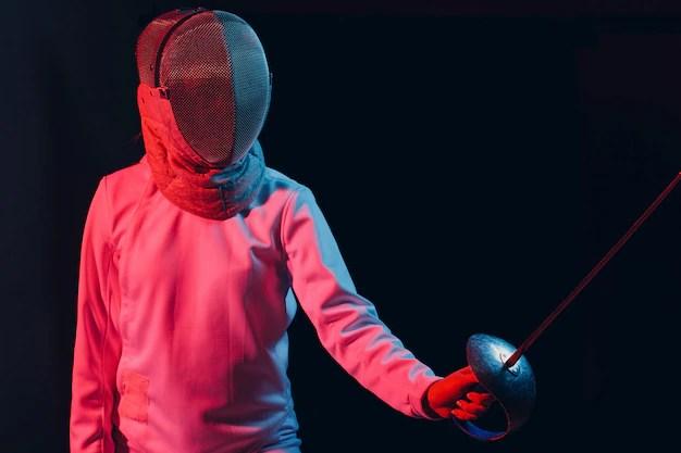 Двое мужчин в фехтовальном костюме тренируются с мечом на ...