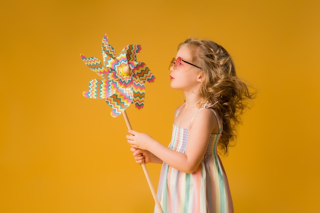 Ребенок девочка улыбается в темных очках, держа ветряную ...