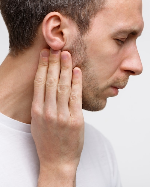 Man touches the lymph glands with his fingers near the ear