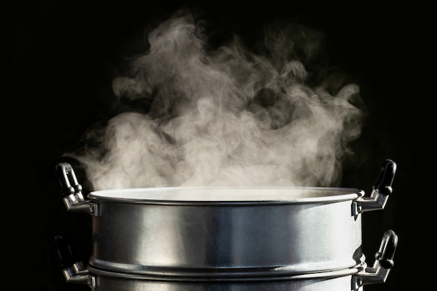 Premium Photo | Traditional steamer pot with white smoke while cooking