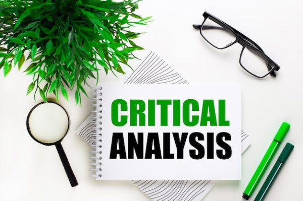 Premium Photo   On a white wall lies a notebook with the word critical  analysis, glasses, a magnifying glass, green markers and a green plant