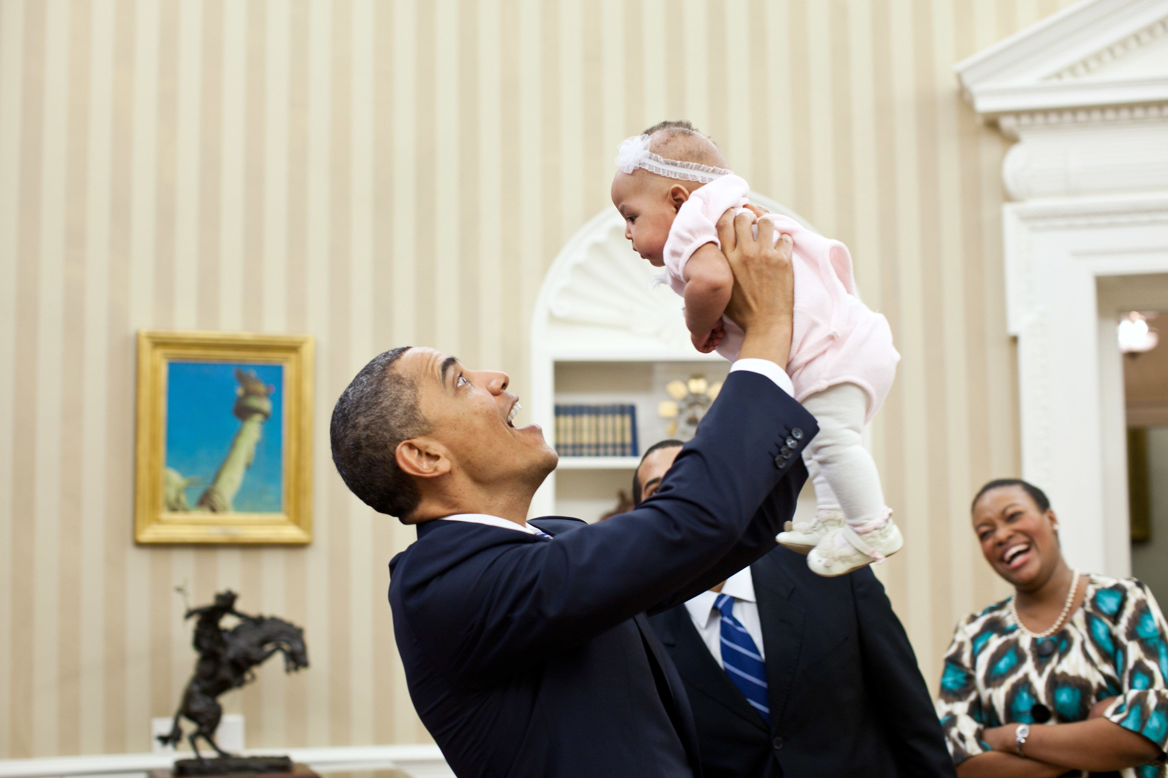 President Barack Obama holds up four-month-old Alia Jawando as her father, William Jawando, Deputy Associate Director of Public Engagement, and her mother Michele look on in the Oval Office, March 9, 2011. (Official White House Photo by Pete Souza)