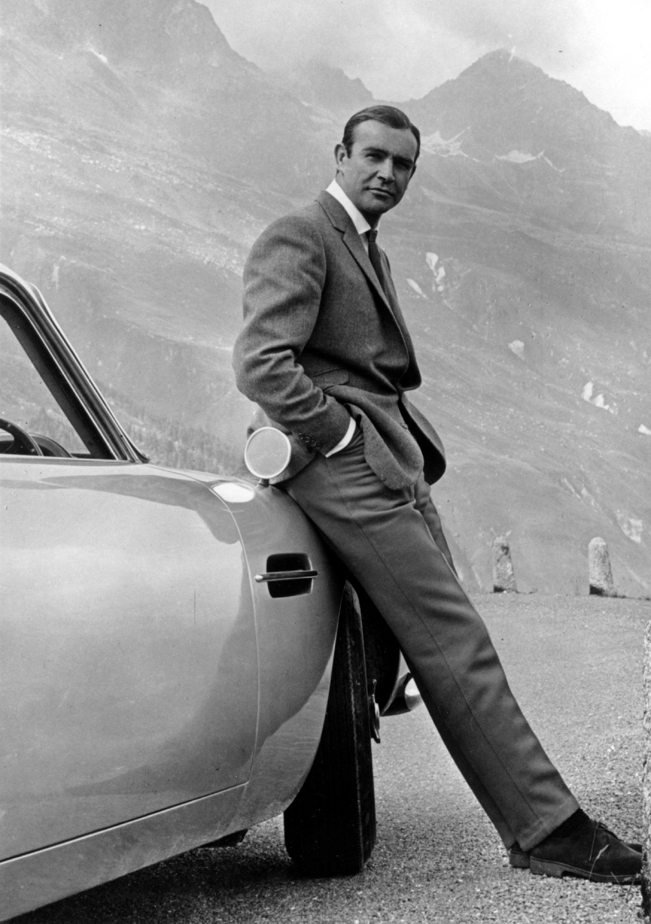 """Connery as James Bond, posing next to his Aston Martin DB5 in a scene from """"Goldfinger."""""""