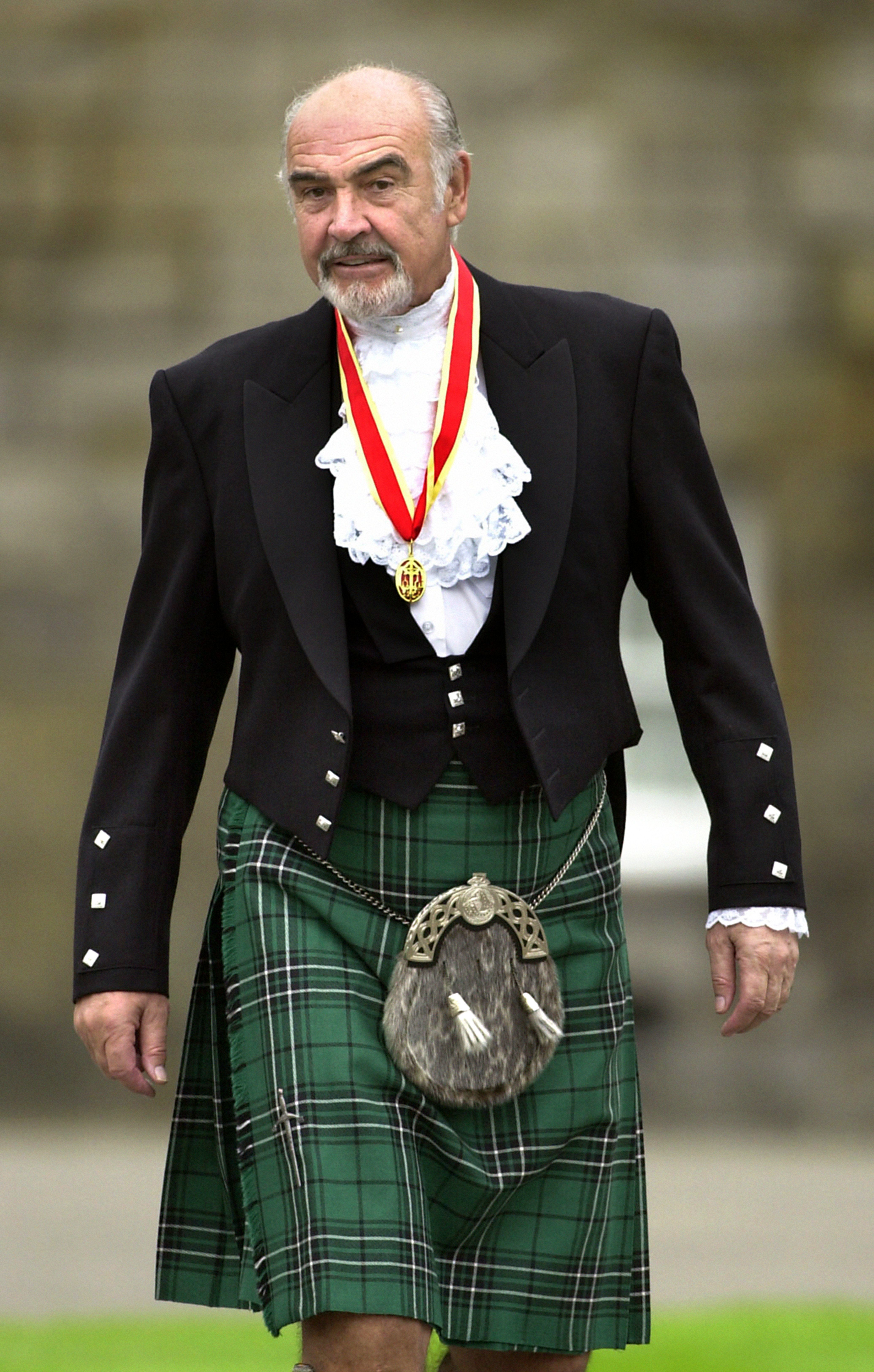 Connery wearsfull Highland dress and his medal after he was formally knighted by the queenin July 2000.
