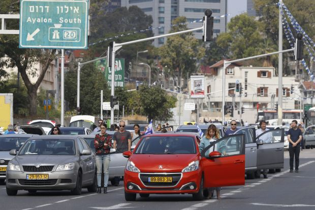 Drivers stop and stand in silence on a street in Tel Aviv.