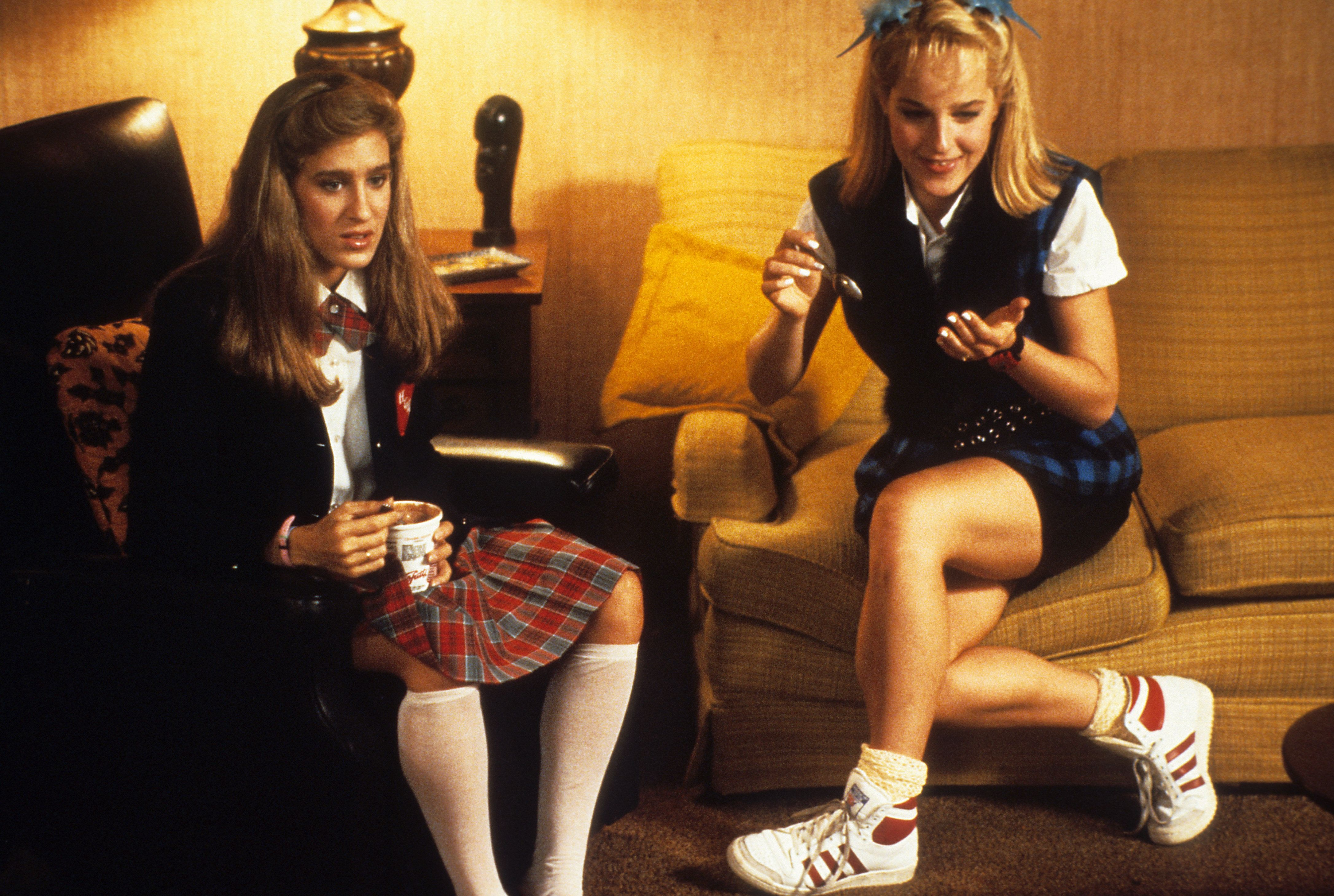 """Sarah Jessica Parker and Helen Hunt watching TV at home in a scene from the film """"Girls Just Want To Have Fun"""" (1985)."""