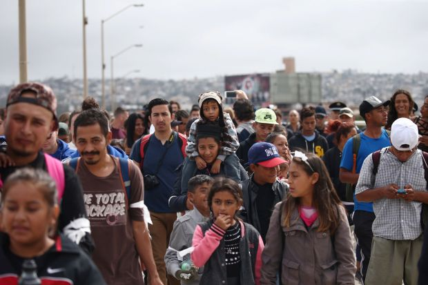 Members of a caravan of migrants from Central America walk towards the United States border.