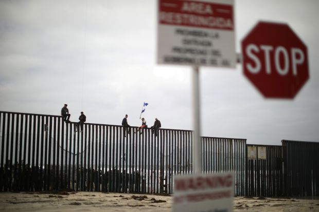 Peoplesit on the top of the U.S.-Mexico border wall.