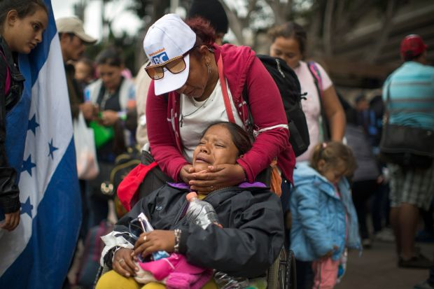 Members of a caravan of Central Americans who spent weeks traveling to the U.S.-Mexico border ask U.S. authorities for asylum