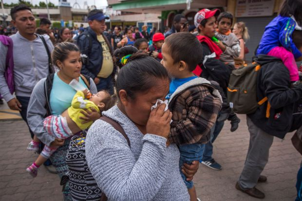 Adults in the migrant caravan carry small children.