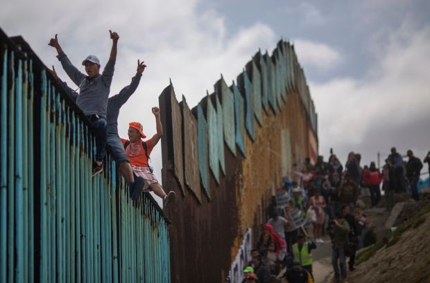 People climb a section of border fence to look into the U.S.
