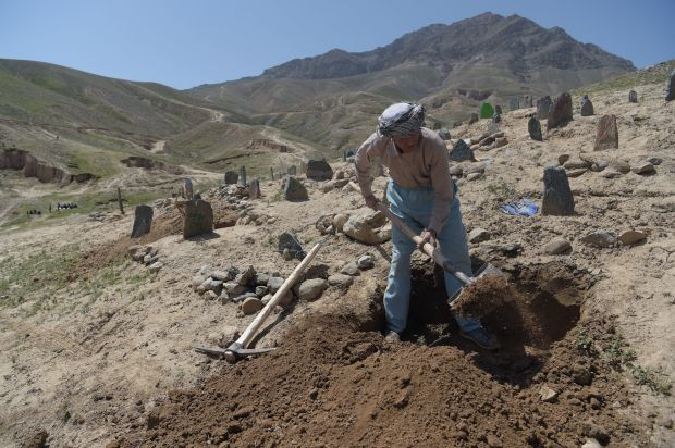 A man digs a grave for one of the 57 victims of a bomb blast on a voter registration center in Kabul on April 23, 2018.