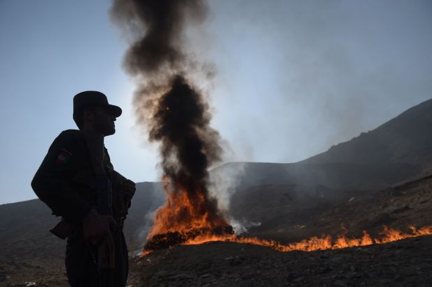 An Afghan policeman watches as a cache of alcohol and drugs burns on the outskirts of Kabul on De. 20, 2016. Ninety-eight ton