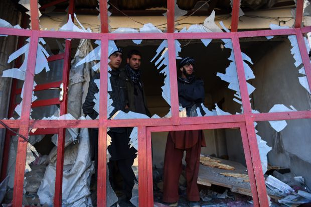 Onlookers peer through the broken windows of a bakery at the site of a suicide car bomb near the international airport in Kab