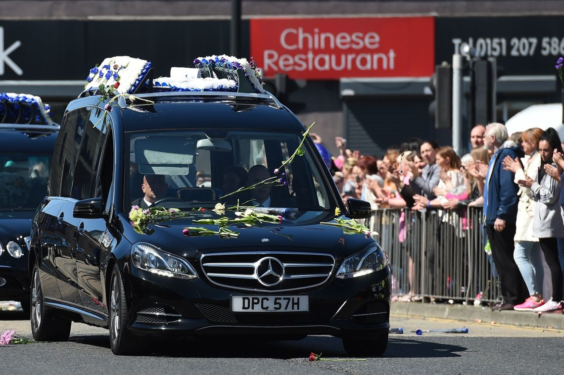 Crowds clapped and threw flowers as the funeral cortege drove past