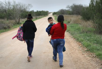 Central American immigrants walk after crossing the U.S.-Mexico border to turn themselves in to Border Patrol agents in Febru