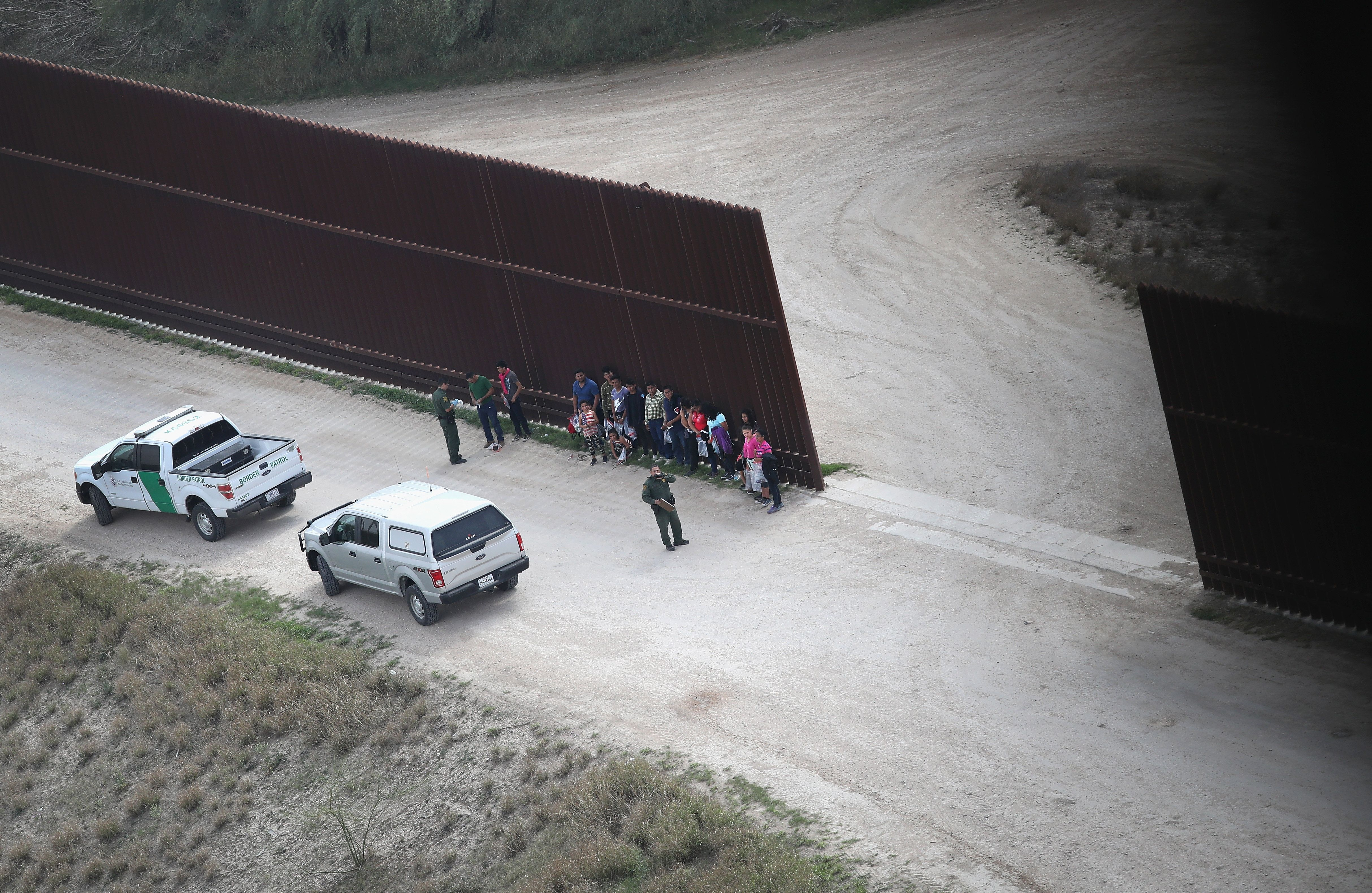 U.S. Border Patrol agents stand with undocumented immigrant families at the U.S.-Mexico border fence before transporting them
