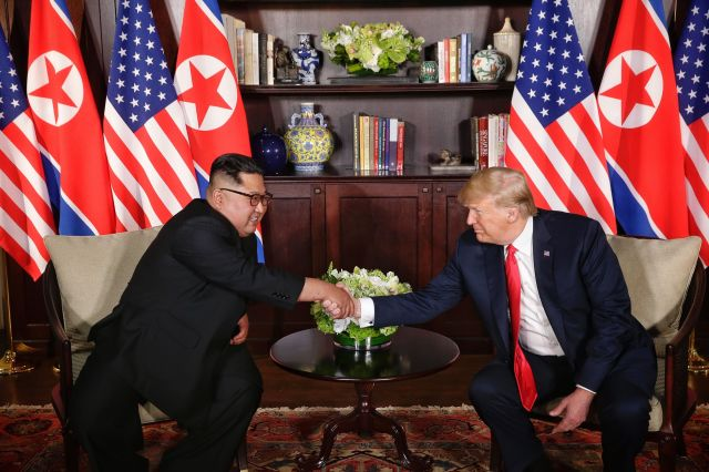 The two leaders pose for a photo op, flanked by American and North Korean flags.