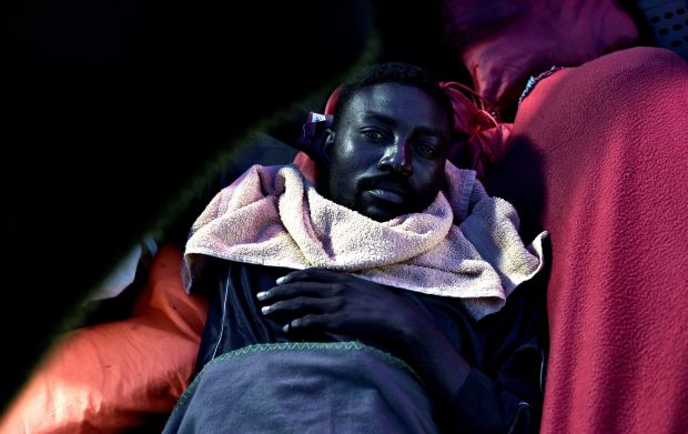A migrant rests on the deck of the Aquarius as the vessel heads towards Spain. He and hundreds of others were turned away fro