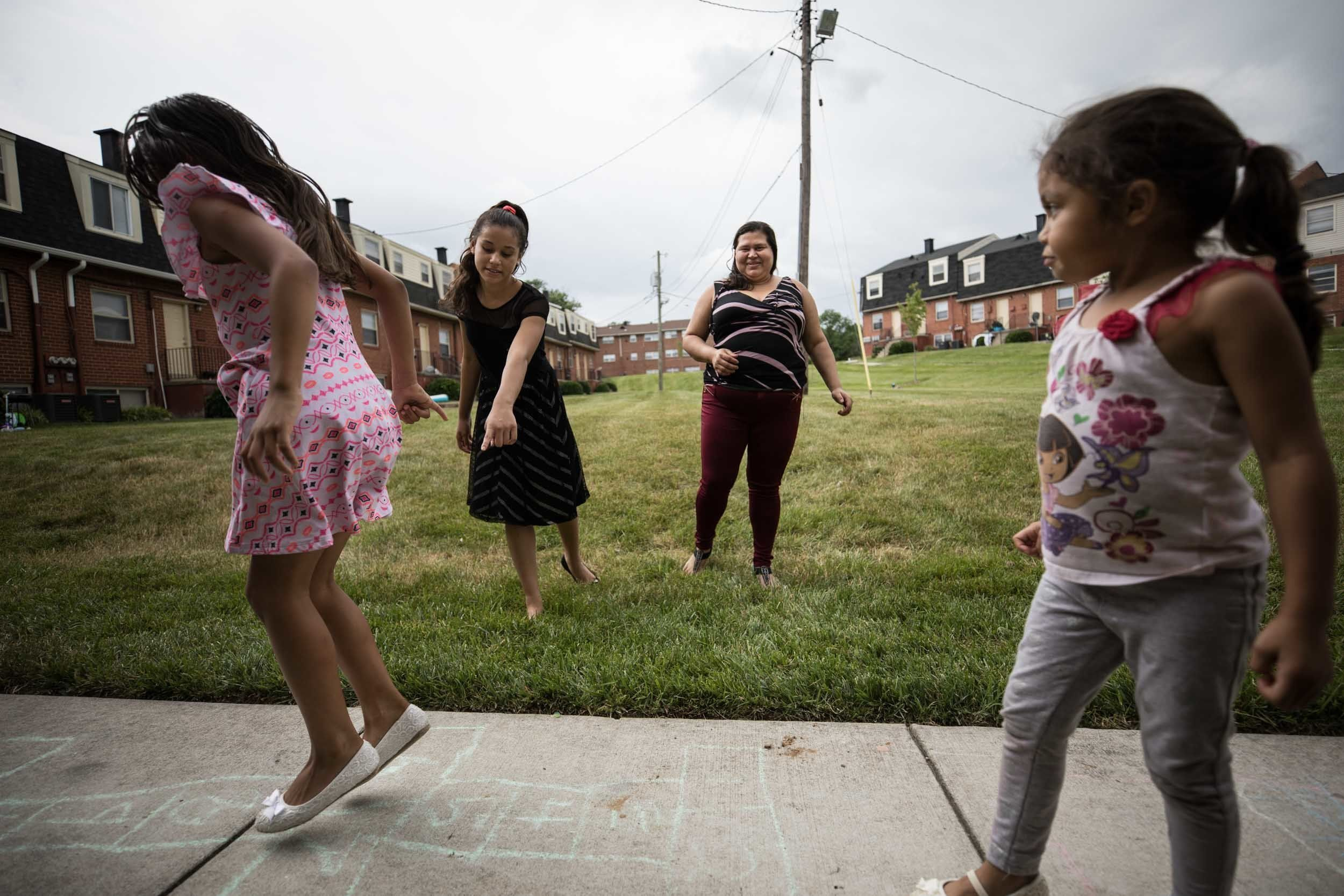 Martinez Yanez watches her daughters playoutside the family's Baltimore apartment.