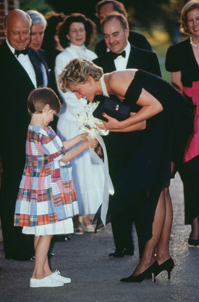 Diana receives a bouquet from a young girl as she arrives for the gala event at the Serpentine Gallery.