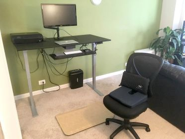 Lunkenheimer's workstation outfitted to help manage his pain with a sit-to-stand desk with raised monitor for correct positio