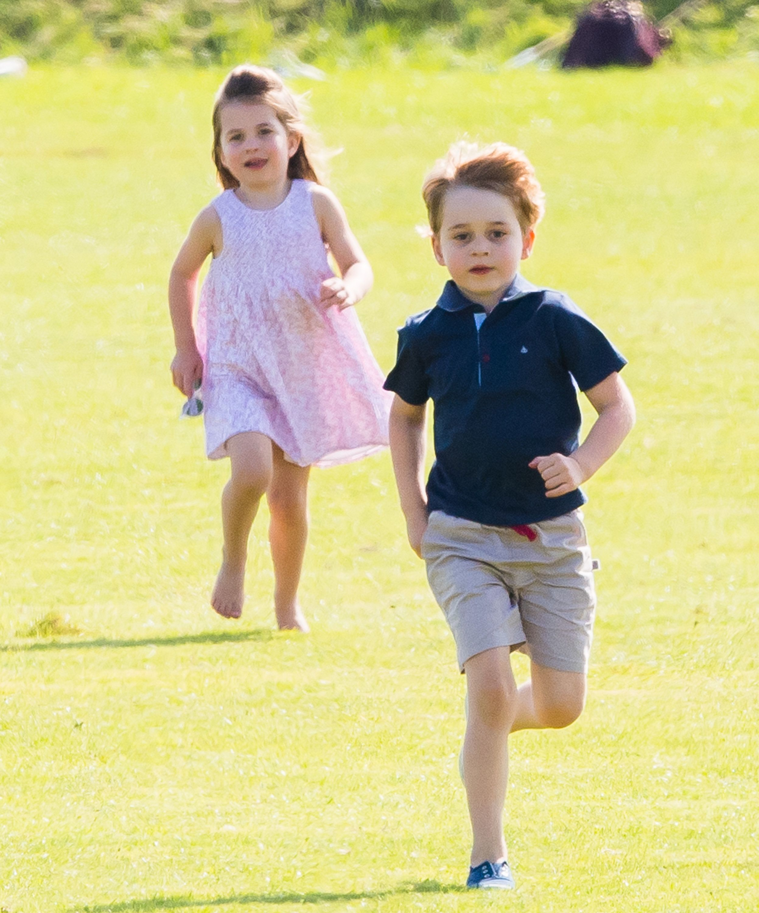 Prince George and Princess Charlotte run together during the Maserati Royal Charity Polo Trophy at Beaufort Park on June 10,