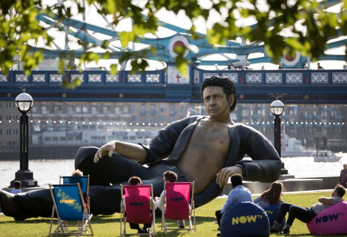 People in lawn chairs marvel at the sexy, lounging statue of actor Jeff Goldblum, which recreates his memorable bare chested