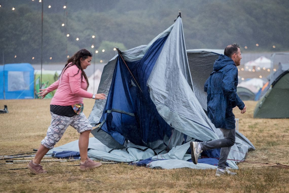 Revellers pack up their tents at the Camp Bestival site in Dorset on Sunday as high winds and rain lashed the festival site.