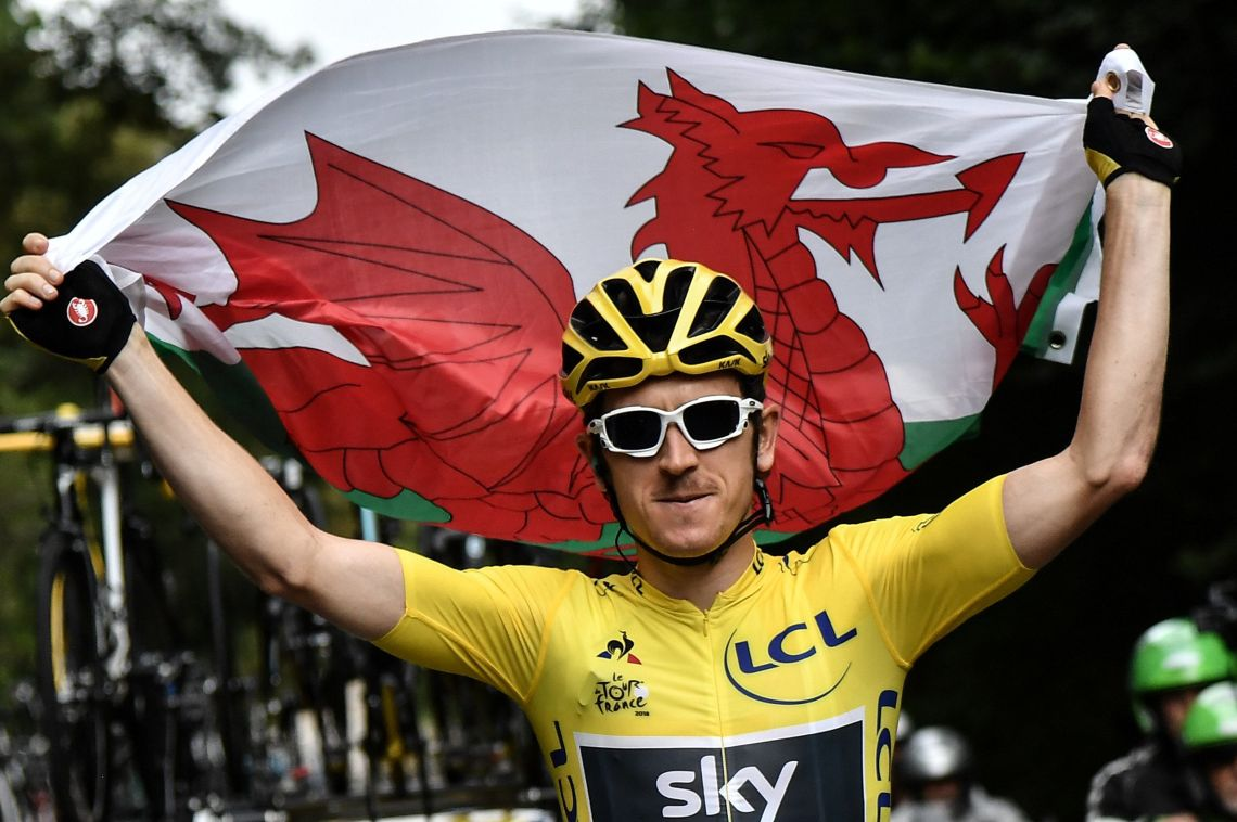 Geraint Thomas wearing the overall leader's yellow jersey, holding the Welsh flag, on the final stage of the Tour de France.