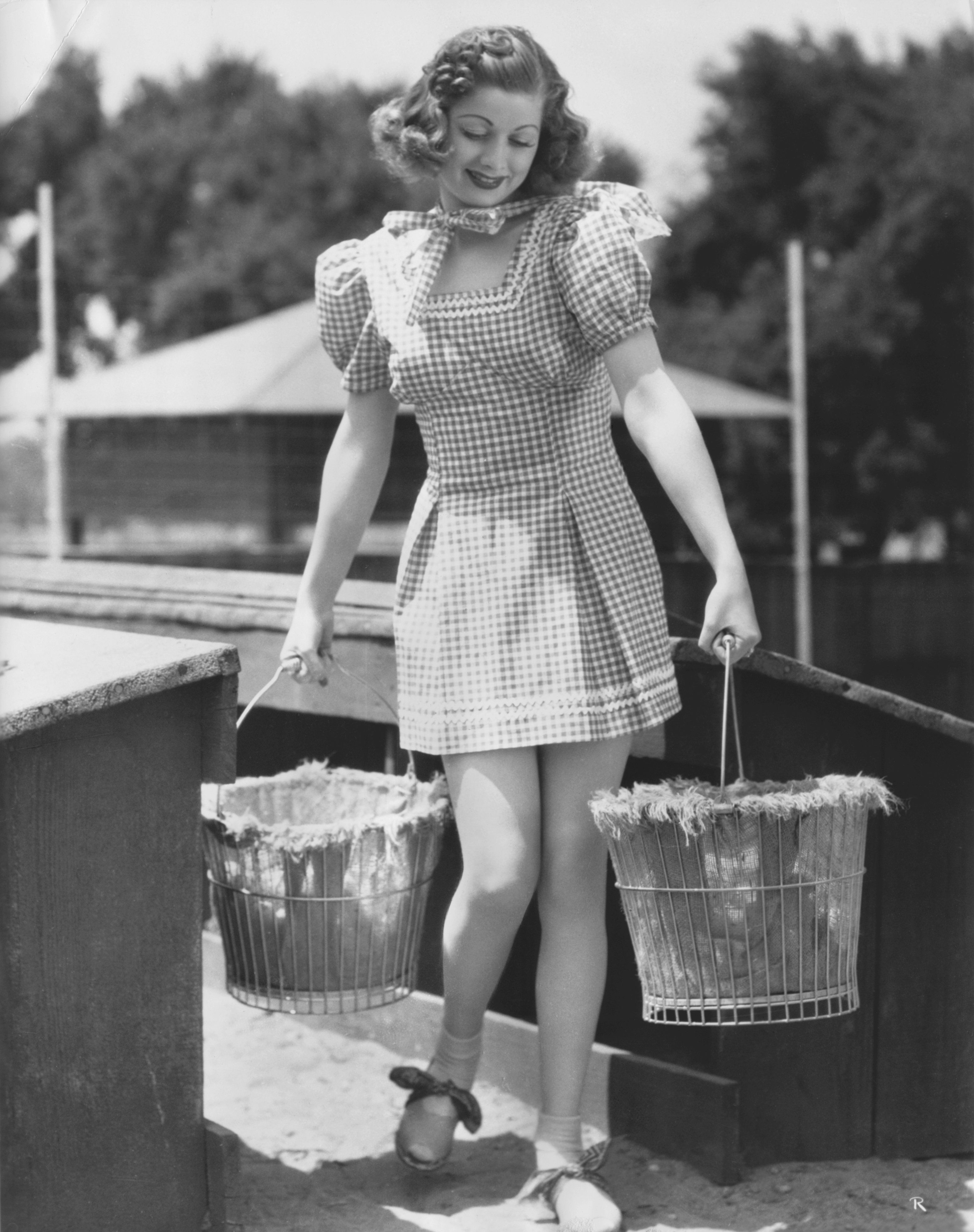 The actress is pictured wearing a gingham dress and carrying egg baskets.
