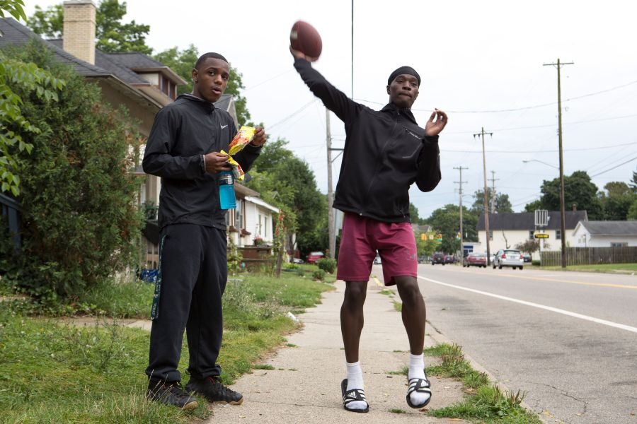 Jones tosses a football while hanging out with his friends in front of his home.