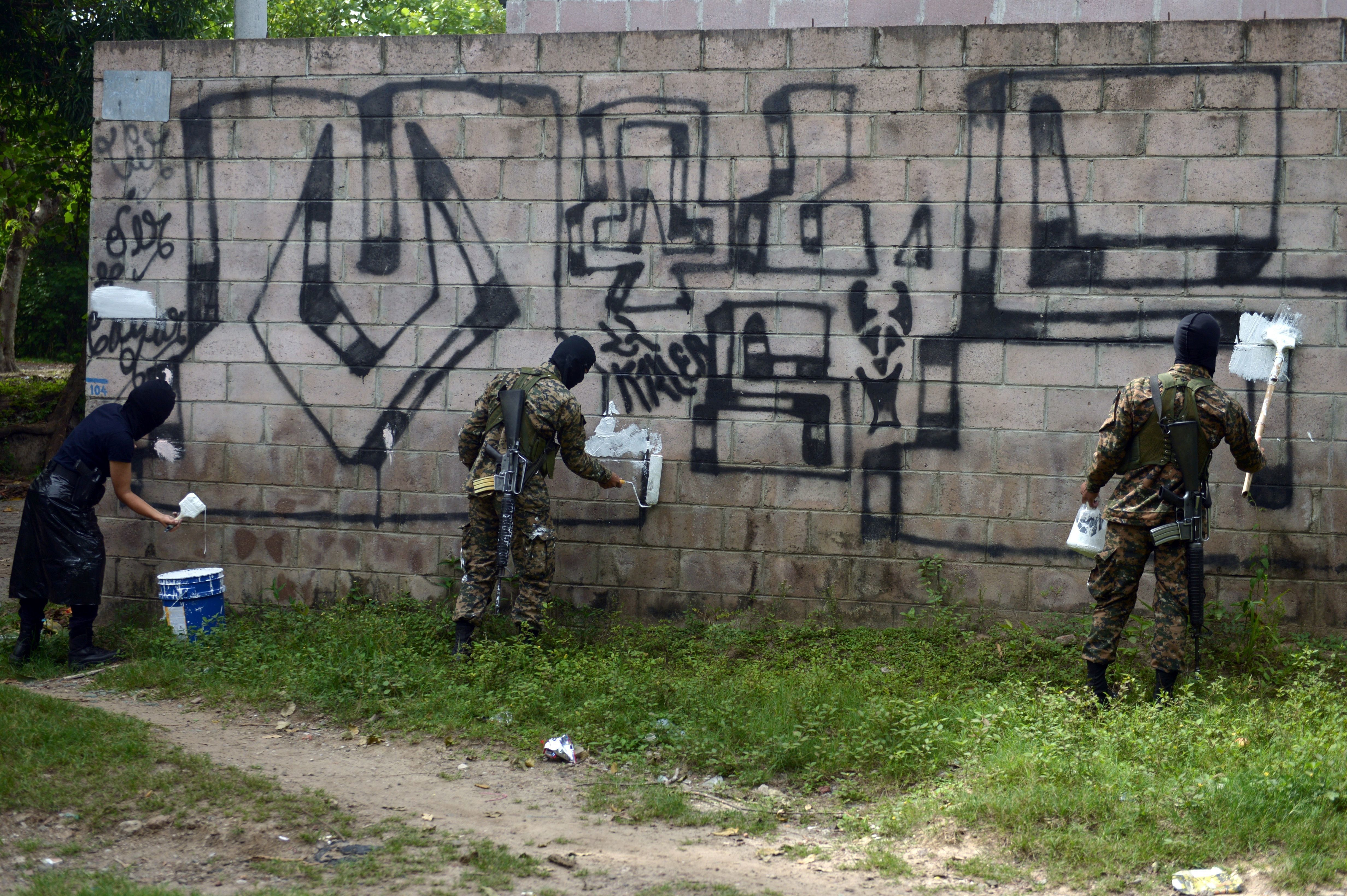 Police officers and soldiers paint over graffiti associated with the Mara Salvatrucha gang, or MS-13, inQuezaltepeque,