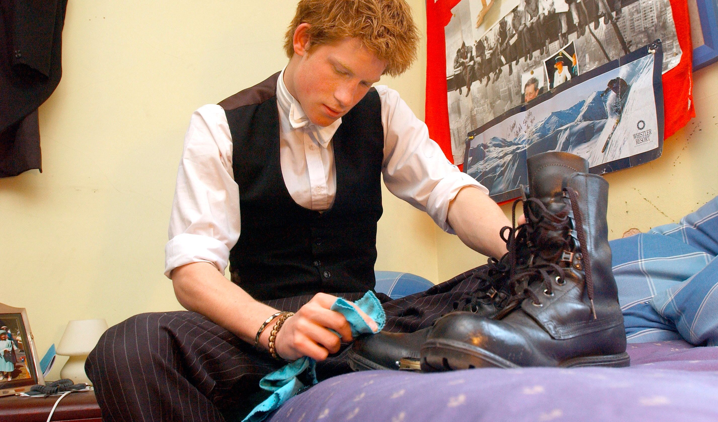 Prince Harry polishes the army boots he wears when participating in the Military Combined Cadet Force.