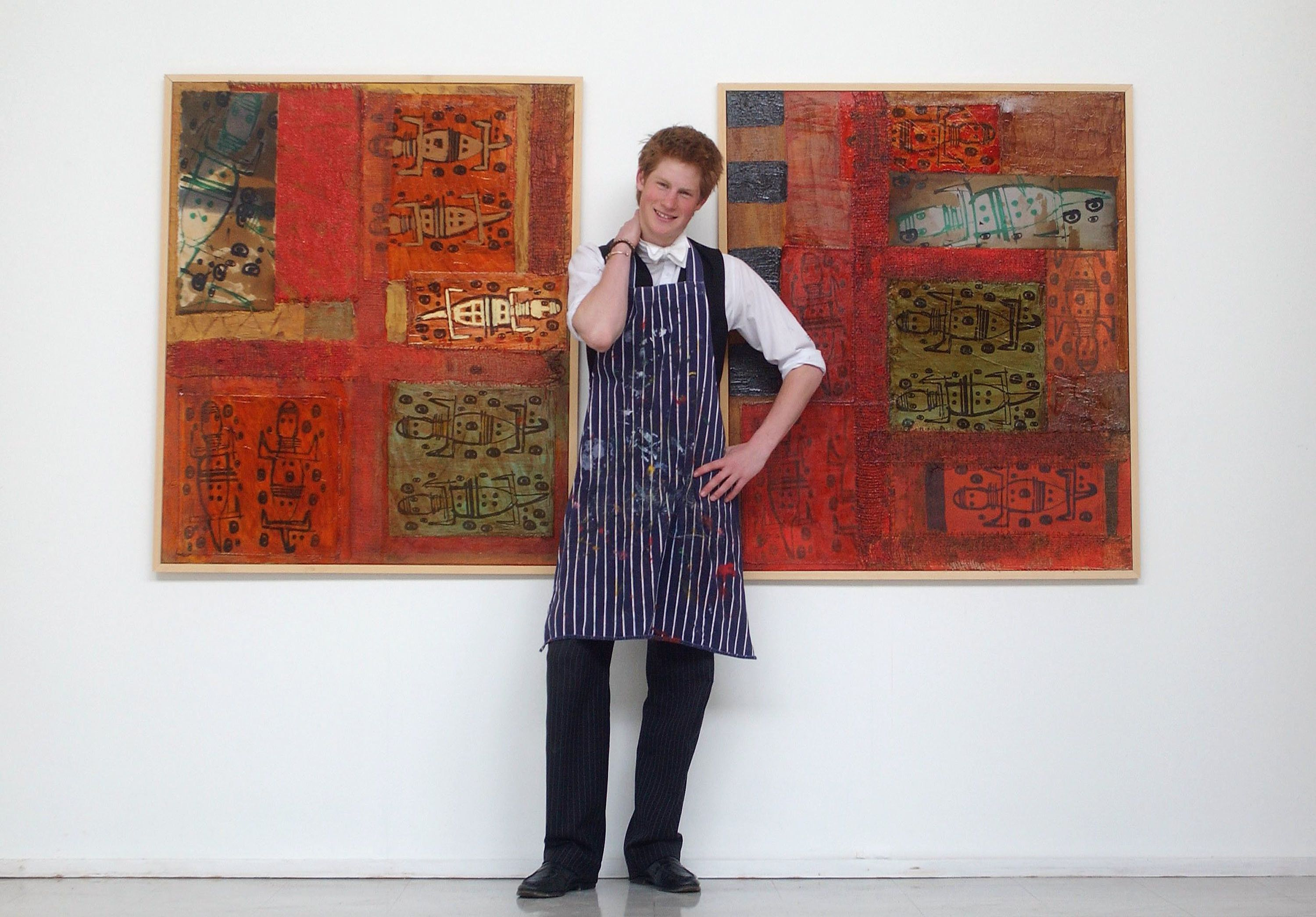 Prince Harry stands between two of his artworks on May 12, 2003, in the Drawing School at Eton College.